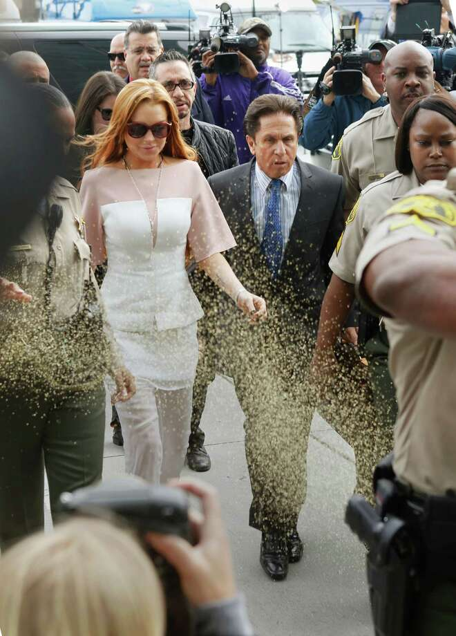 Actress Lindsay Lohan is showered with gold glitter, left, as she walks with her attorney Mark Heller, to attend a trial Monday, March 18, 2013, at  Los Angeles Superior court. Lohan is charged with three misdemeanor counts stemming from a crash on Pacific Coast Highway. She is charged with willfully resisting, obstructing or delaying an officer, providing false information to an officer and reckless driving. She is also accused of violating her probation in a misdemeanor jewelry theft case. Photo: AP