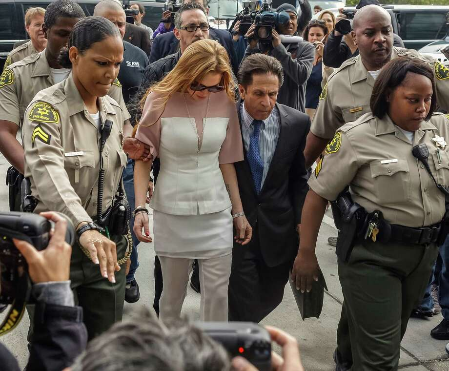 Actress Lindsay Lohan is escorted by Los Angeles County sheriffs as she arrives for her trial with her attorney Mark Heller, on Monday, March 18, 2013. Lohan is charged with three misdemeanor counts stemming from a crash on Pacific Coast Highway. She is charged with willfully resisting, obstructing or delaying an officer, providing false information to an officer and reckless driving. She is also accused of violating her probation in a misdemeanor jewelry theft case. Photo: AP