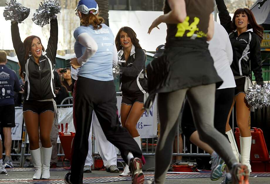 Oakland Raider cheerleaders welcomed 5K runners back to the finish line. The 2013 Oakland Running Festival featured a marathon, half marathon, relays, a 5K race and kids fun run all over the city on a fine spring day Sunday March 24, 2013. Photo: Brant Ward, The Chronicle