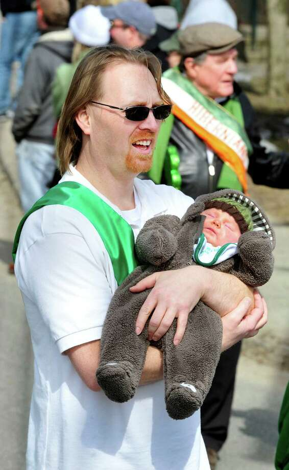 Paul Grasseler and his daughter Coeli, 9 months, march with the Ancient Order of Hibernians in Danbury's St. Patrick's Day Parade and Danbury Whalers Commissioner's Cup victory celebration Sunday, March 24, 2013 in Conn. Photo: Michael Duffy / The News-Times