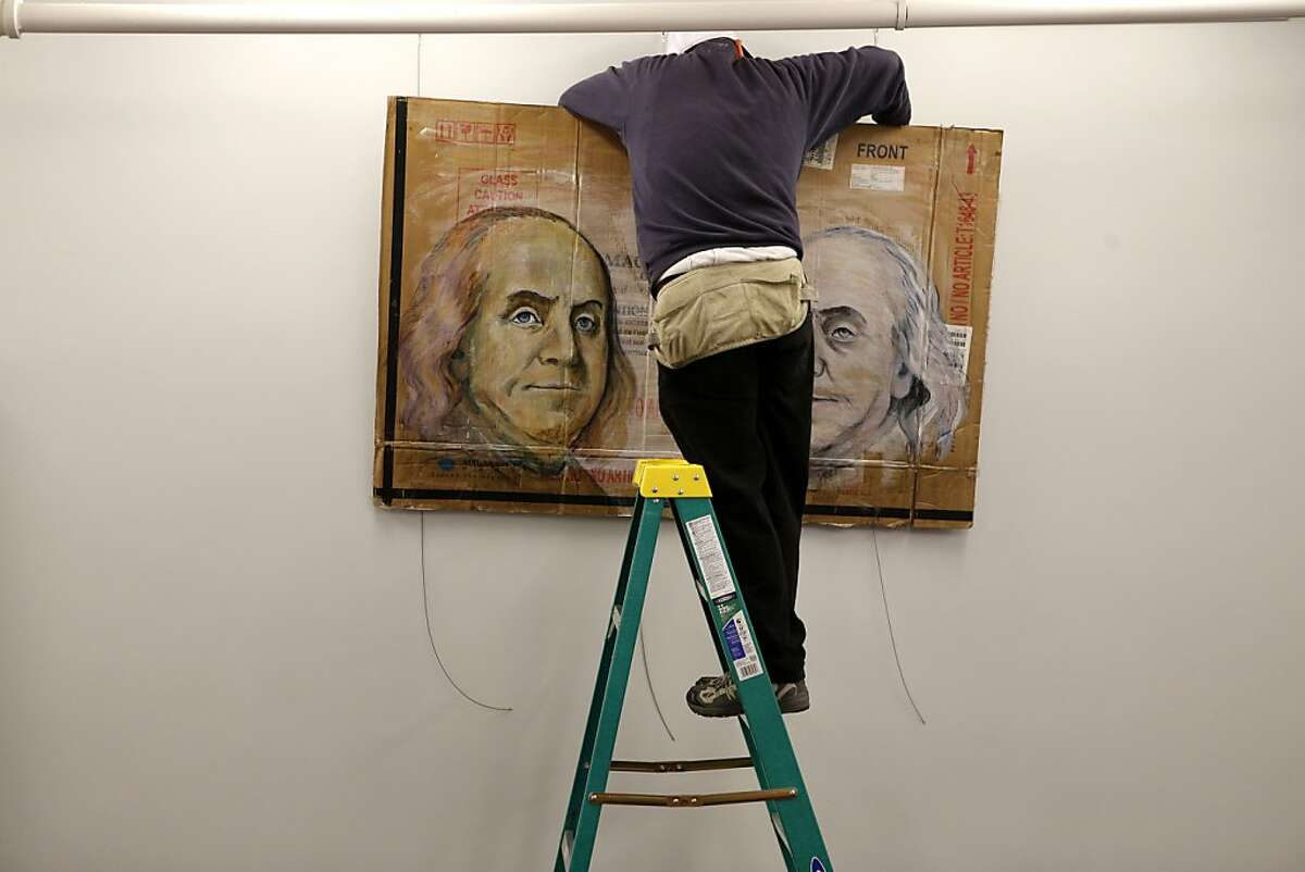 Caleb Lefkowitz, of Santa Rosa, hangs art for his artist friend Nick Mancillas at the Capital One 360 cafe Friday, March 22, 2013 in San Francisco, Calif.