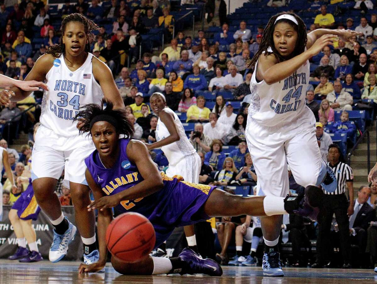 Albany forward Shereesha Richards, bottom, loses possession of the ball as she is pressured by North Carolina forward Xylina McDaniel, top left, and guard Tierra Ruffin-Pratt during the first half of a first-round game in the women's NCAA college basketball tournament in Newark, Del., Sunday, March 24, 2013. (AP Photo/Patrick Semansky)