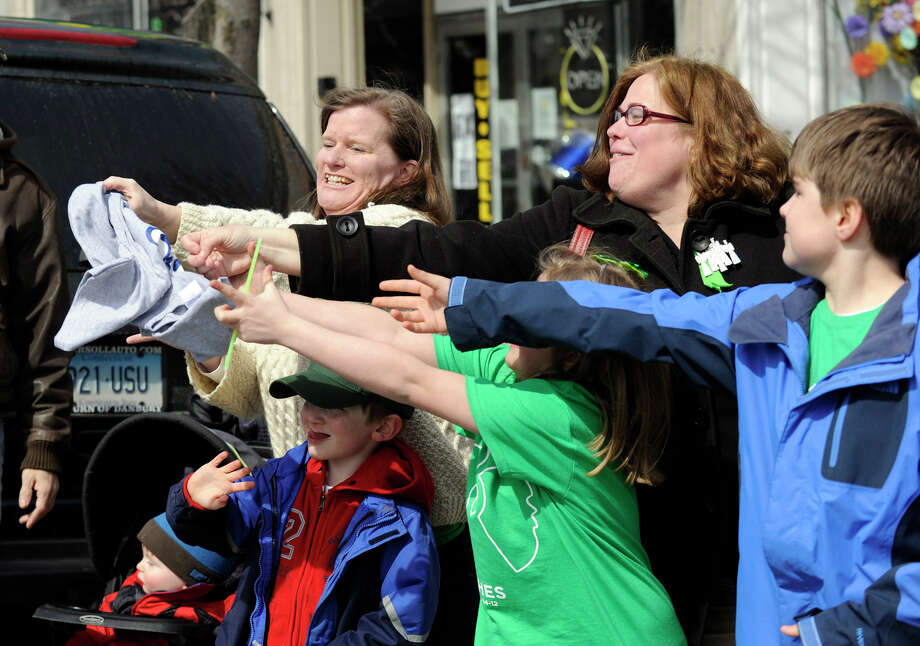 Onlookers grab a Danbury Whaler's T-shirt tossed their way from the Whaler's float at Sunday's parade. The Danbury Whalers joined the St. Patrick's Day Parade to celebrate their Commissioner's Cup win Friday night. The parade started at St. Peter Church on Main street and ended at  the Irish Cultural Center on West Street in Danbury, Conn., Sunday, March 24, 2013. Photo: Carol Kaliff / The News-Times