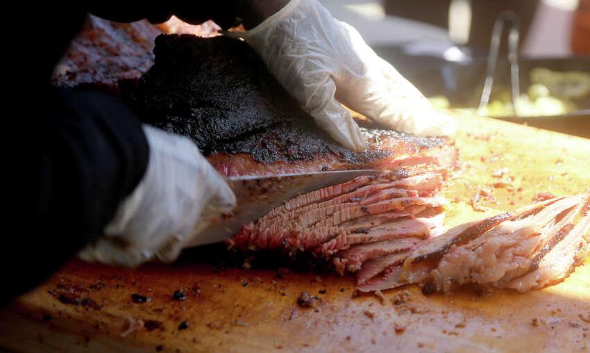 Ken Gatlin slices brisket at the Gatlin's BBQ tent.