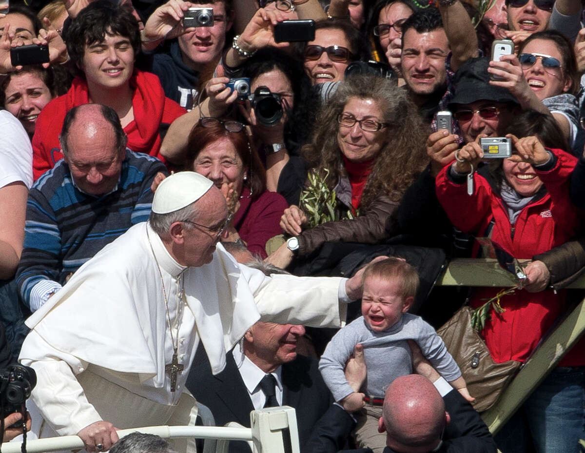 Pope Francis pats a crying child after celebrating his first Palm Sunday Mass, in St. Peter's Square, at the Vatican, Sunday, March 24, 2013. Pope Francis celebrated his first Palm Sunday Mass in St. Peter's Square, encouraging people to be humble and young at heart, as tens of thousands joyfully waved olive branches and palm fronds. The square overflowed with some 250,000 pilgrims, tourists and Romans eager to join the new pope at the start of solemn Holy Week ceremonies, which lead up to Easter, Christianity's most important day (AP Photo/Alessandra Tarantino)