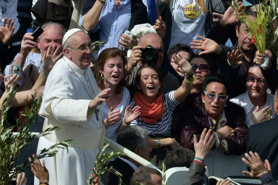 Pope Francis waves to the crowd after a mass on St Peter's square as part of the Palm Sunday celebration on March 24, 2013 at the Vatican. The Palm Sunday marks the start of the holy week of Easter in celebration of the crucifixion and resurrection of Jesus Christ.    AFP PHOTO / GABRIEL BOUYSGABRIEL BOUYS/AFP/Getty Images Photo: GABRIEL BOUYS, AFP/Getty Images / AFP