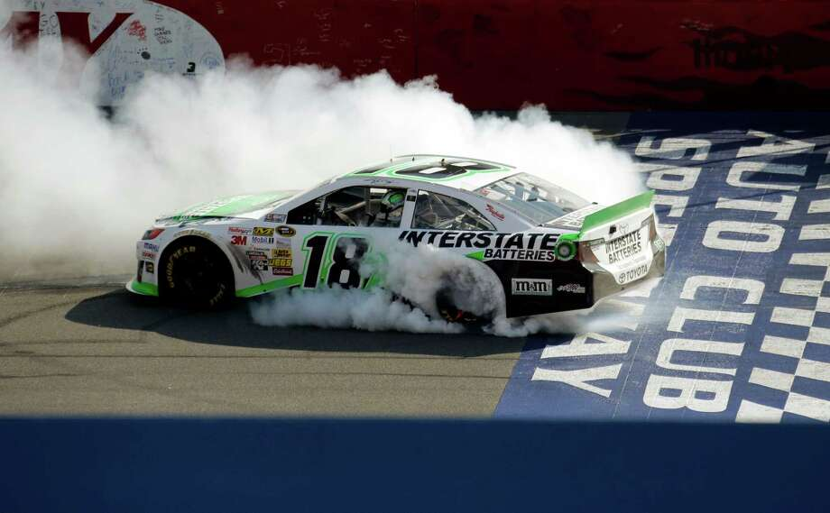 Kyle Busch performs a burnout after winning the NASCAR Sprint Cup Series auto race in Fontana, Calif., Sunday, March 24, 2013. (AP Photo/Reed Saxon) Photo: Reed Saxon
