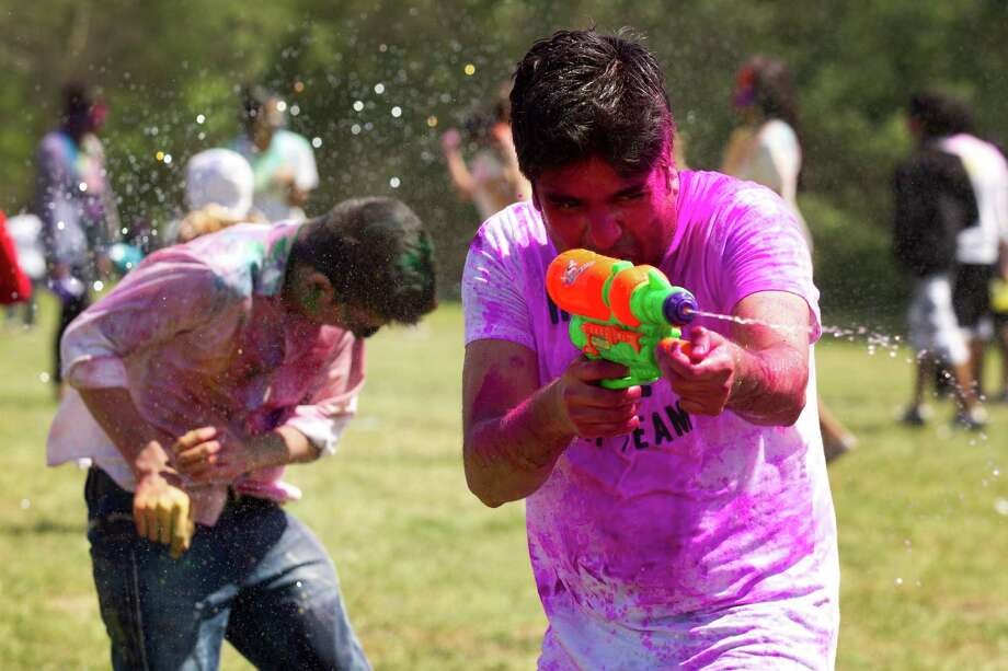 Revelers spray water on each other with water guns to celebrate Holi at Seabourne Creek Park Sunday, March 24, 2013, in Rosenberg. Photo: Brett Coomer, Houston Chronicle / © 2013 Houston Chronicle