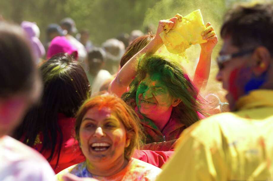 Revelers have color powder poured on them as they celebrate Holi at Seabourne Creek Park Sunday, March 24, 2013, in Rosenberg. Holi, a festival of color, celebrates spring. Photo: Brett Coomer, Houston Chronicle / © 2013 Houston Chronicle