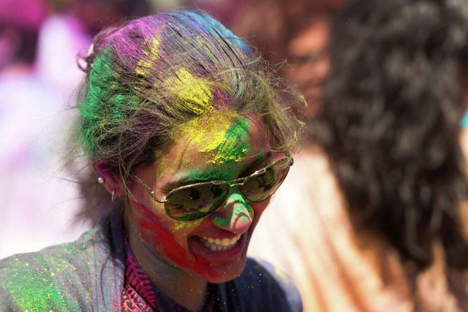 A reveler is covered in colored powder during the celebration of Holi at Seabourne Creek Park Sunday, March 24, 2013, in Rosenberg. Holi, a festival of color, celebrates spring. Photo: Brett Coomer, Houston Chronicle / © 2013 Houston Chronicle