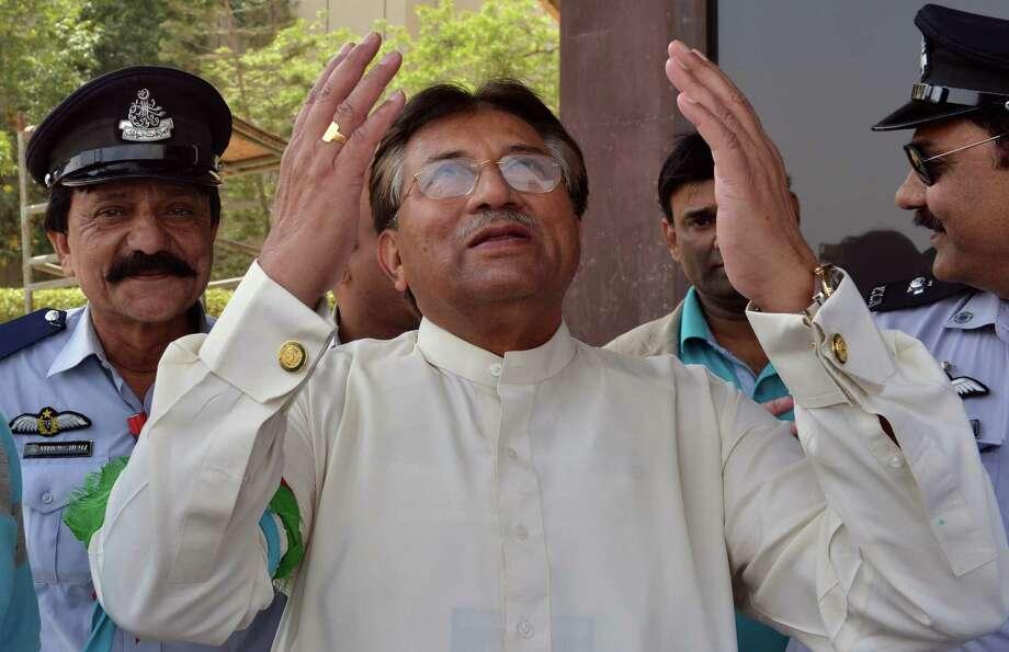 Former Pakistan President Pervez Musharraf prays upon arrival Sunday at the Karachi International airport. He left Pakistan after resigning in 2008. Photo: AAMIR QURESHI, Staff / AFP