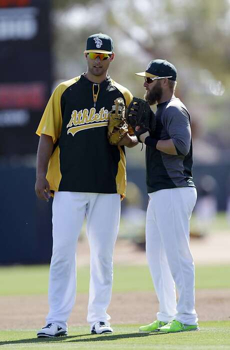 Oakland Athletics' Nate Freiman, left, talks with teammate Daric Barton before an exhibition spring training baseball game against the Los Angeles Dodgers, Sunday, March 24, 2013, in Phoenix. (AP Photo/Marcio Jose Sanchez) Photo: Marcio Jose Sanchez, Associated Press