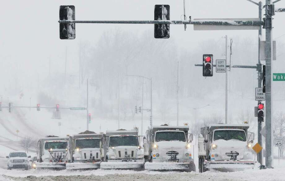 Snow plows stop for a traffic signal as they clear several lanes of West 6th Street in Lawrence, Kan., Sunday, March 24, 2013. Few signs of spring are being found in parts of the Midwest as a snowstorm brings heavy snow and high winds. (AP Photo/Orlin Wagner) Photo: Orlin Wagner, STF / AP