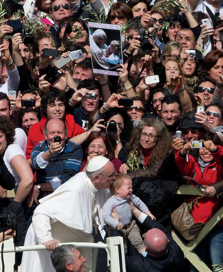Pope Francis kisses a baby after celebrating his first Palm Sunday Mass, in St. Peter's Square, at the Vatican, Sunday, March 24, 2013. Pope Francis celebrated his first Palm Sunday Mass in St. Peter's Square, encouraging people to be humble and young at heart, as tens of thousands joyfully waved olive branches and palm fronds. The square overflowed with some 250,000 pilgrims, tourists and Romans eager to join the new pope at the start of solemn Holy Week ceremonies, which lead up to Easter, Christianity's most important day (AP Photo/Alessandra Tarantino) Photo: Alessandra Tarantino, Associated Press / AP
