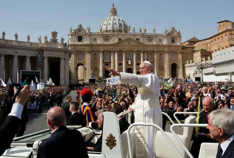 Pope Francis greets the crowd gathered for the Palm Sunday Mass in St. Peter's Square at the Vatican, Sunday, March 24, 2013. Pope Francis celebrated his first Palm Sunday Mass in St. Peter's Square, encouraging people to be humble and young at heart, as tens of thousands joyfully waved olive branches and palm fronds. (AP Photo/Domenico Stinellis) Photo: Domenico Stinellis, Associated Press / AP