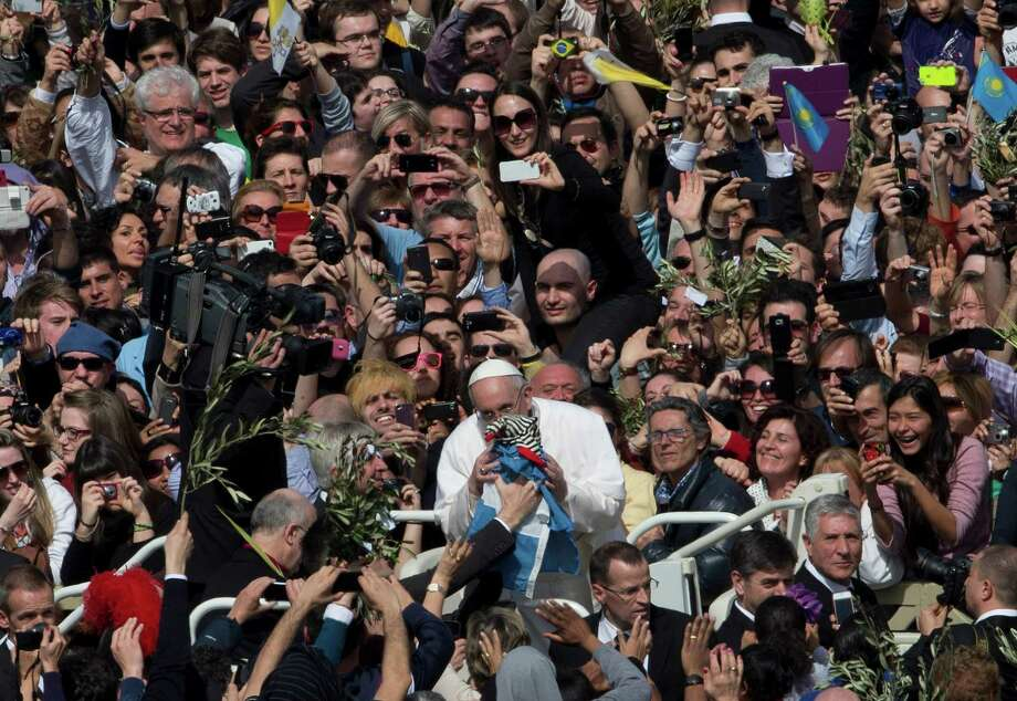 Pope Francis kisses a child after celebrating his first Palm Sunday Mass, in St. Peter's Square, at the Vatican, Sunday, March 24, 2013. Pope Francis celebrated his first Palm Sunday Mass in St. Peter's Square, encouraging people to be humble and young at heart, as tens of thousands joyfully waved olive branches and palm fronds. The square overflowed with some 250,000 pilgrims, tourists and Romans eager to join the new pope at the start of solemn Holy Week ceremonies, which lead up to Easter, Christianity's most important day. (AP Photo/Alessandra Tarantino) Photo: Alessandra Tarantino, Associated Press / AP