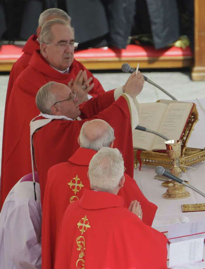 Pope Francis celebrats his first Palm Sunday Mass, in St. Peter's Square, at the Vatican, Sunday, March 24, 2013. Pope Francis celebrated his first Palm Sunday Mass in St. Peter's Square, encouraging people to be humble and young at heart, as tens of thousands joyfully waved olive branches and palm fronds. The square overflowed with some 250,000 pilgrims, tourists and Romans eager to join the new pope at the start of solemn Holy Week ceremonies, which lead up to Easter, Christianity's most important day (AP Photo/Andrew Medichini) Photo: Andrew Medichini, Associated Press / AP