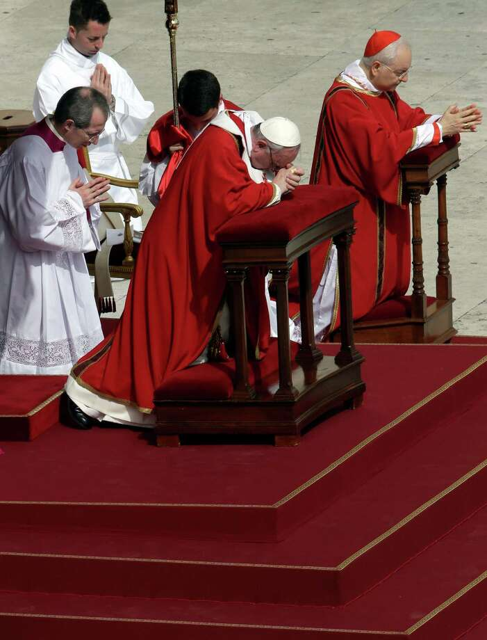 Pope Francis kneels in prayer as he celebrates Palm Sunday Mass, in St. Peter's Square at the Vatican, Sunday, March 24, 2013. The new pontiff arrived in an uncovered vehicle to start solemn Holy Week ceremonies, which lead up to Easter, Christianity's most important day. Francis wore bright red robes over a white cassock and presided over the Mass from an altar sheltered by a canopy on the steps of St. Peter's Basilica. (AP Photo/Alessandra Tarantino) Photo: Alessandra Tarantino, Associated Press / AP