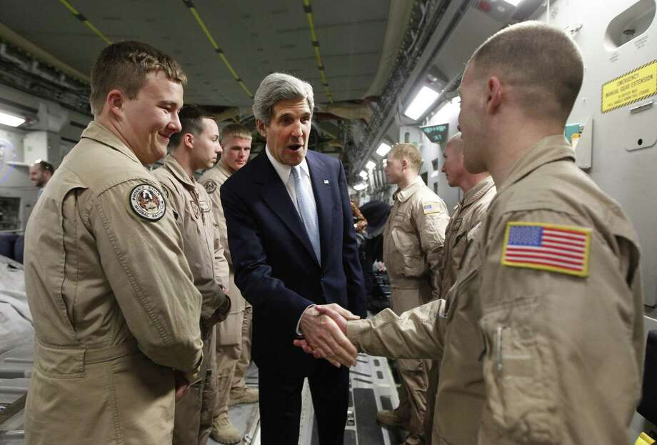 John Kerry, greeting Air Force airmen in the Middle East, is seeking Iraqi Prime Minister Nouri al-Maliki's help in preventing Iran from flying arms aid to Syria through Iraq's airspace. Photo: Jason Reed / Getty Images