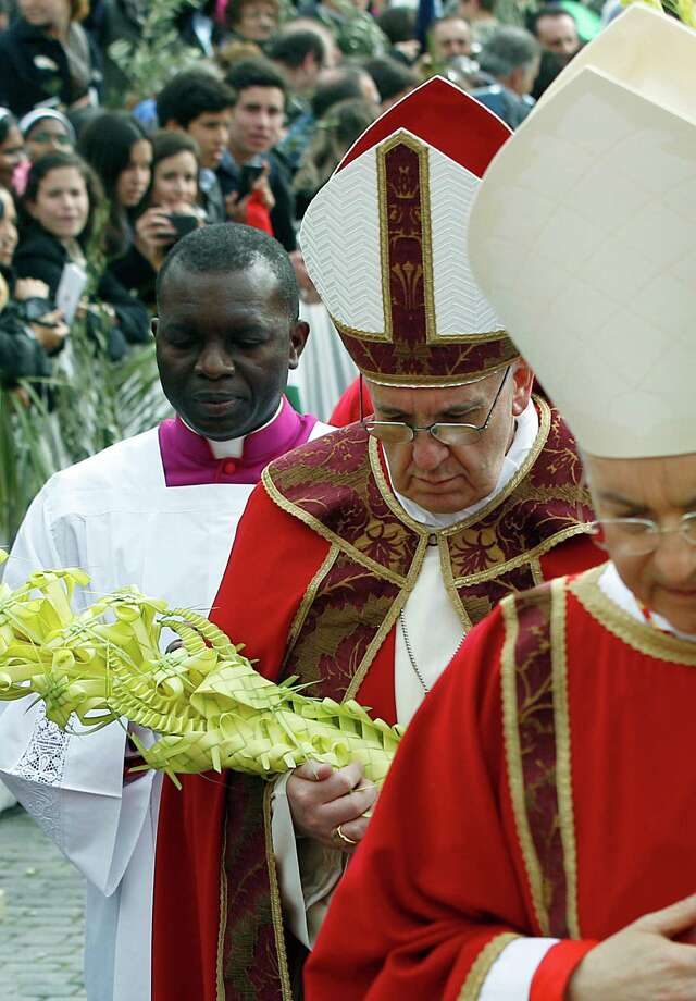 Pope Francis celebrates Palm Sunday Mass, in St. Peter's Square at the Vatican, Sunday, March 24, 2013. The new pontiff arrived in an uncovered vehicle to start solemn Holy Week ceremonies, which lead up to Easter, Christianity's most important day. Francis wore bright red robes over a white cassock and presided over the Mass from an altar sheltered by a canopy on the steps of St. Peter's Basilica. (AP Photo/Andrew Medichini) Photo: Andrew Medichini, Associated Press / AP