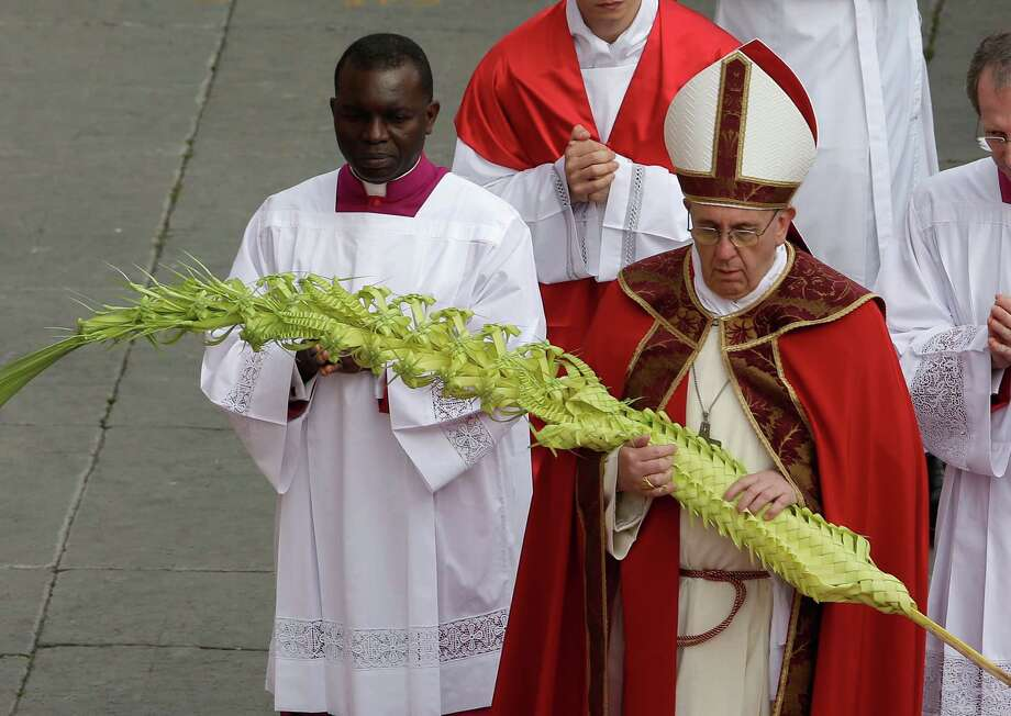 Pope Francis arrives to celebrate Palm Sunday Mass, in St. Peter's Square at the Vatican, Sunday, March 24, 2013. The new pontiff arrived in an uncovered vehicle to start solemn Holy Week ceremonies, which lead up to Easter, Christianity's most important day. Francis wore bright red robes over a white cassock and presided over the Mass from an altar sheltered by a canopy on the steps of St. Peter's Basilica. (AP Photo/Alessandra Tarantino) Photo: Alessandra Tarantino, Associated Press / AP