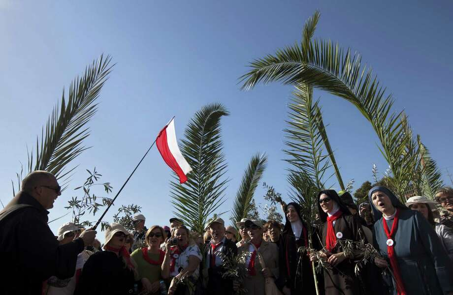 A pilgrim waves a Polish flag as others hold palm fronds during the Palm Sunday procession on the Mount of Olives overlooking Jerusalem's old city. Photo: Sebastian Scheiner / Associated Press