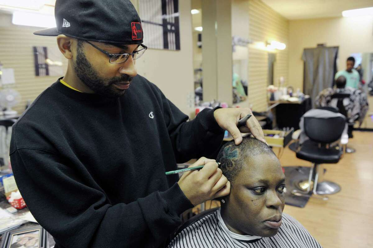 Joseph Johnson, owner of Mr. J's Barber Shop in the Mont Pleasant area of Schenectady, colors in a shamrock he created with clippers in the hair of customer Lisa Johnson (no relation) on Tuesday, March 12, 2013. (Paul Buckowski / Times Union)