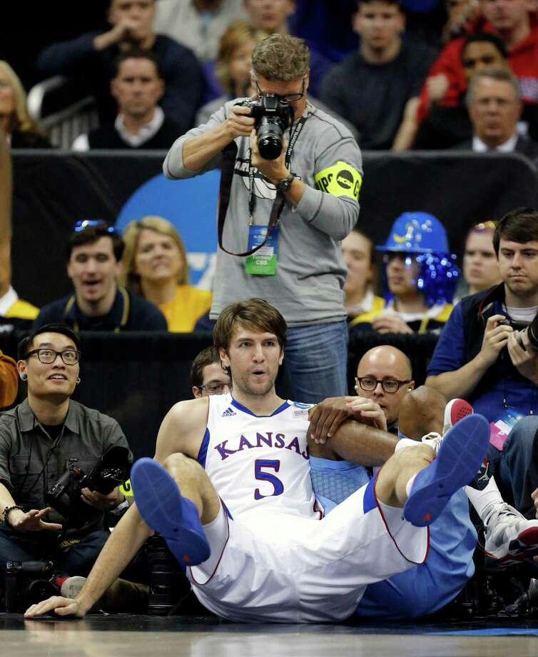 Kansas center Jeff Withey (5) lands amidst photographers during the second half of a third-round game against North Carolina in the NCAA college basketball tournament at the Sprint Center in Kansas City, Mo., Sunday, March 24, 2013. Kansas defeated North Carolina 70-58. (AP Photo/Orlin Wagner) Photo: Orlin Wagner