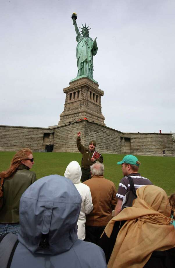 NEW YORK - MAY 18:  A National Park Service guide speaks to a tour group set on Liberty Island in the New York Harbor on May 18, 2009 in New York City. Enhanced security around the statue and improvements at nearby Ellis Island are being funded by a $25 million grant provided by the American Recovery and Reinvestment Act. The National Park Service has received huge grants of stimulus funds for improvements and repairs to parks across the nation. Many of the projects including at the Statue of Liberty, however, have yet to begin partly due to the bureaucracy of awarding commercial contracts with such large sums of money.  (Photo by John Moore/Getty Images) Photo: John Moore / 2009 Getty Images