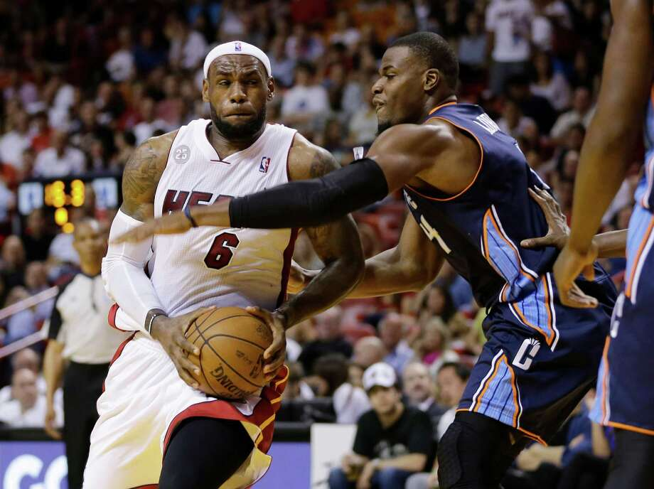 Miami Heat's LeBron James (6) drives around Charlotte Bobcats' Jeff Adrien (4) looking for a shot during the first half of an NBA basketball game in Miami, Sunday  March 24, 2013. (AP Photo/J Pat Carter) Photo: J Pat Carter