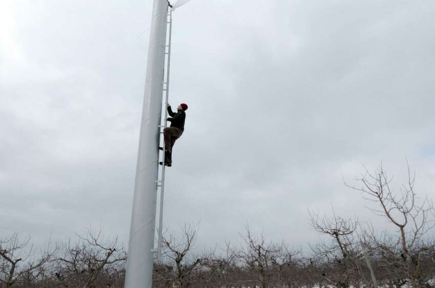 Derek Grout, marketing manager for Golden Harvest Farms climbs up one of the orchard fans on Wednesday, March 20, 2013 in Valatie, NY. The orchard has installed six orchard fan systems to help keep the trees from being damaged during the flowering season because of cold temperatures. Each fan can circulate air for about 15 acres. The fans will only be effective if there is a temperature inversion. (Paul Buckowski / Times Union)