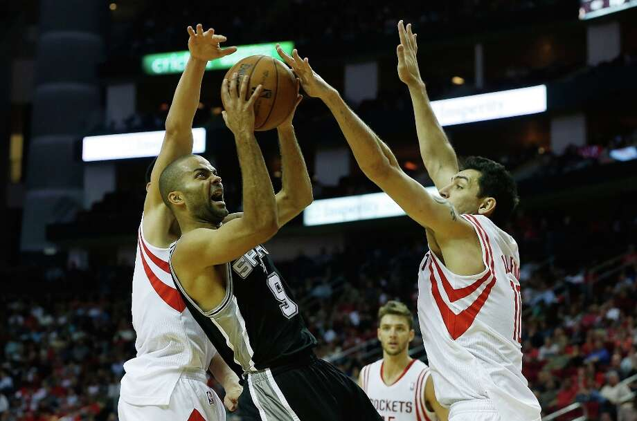 Tony Parker (9) of the Spurs is defended by Jeremy Lin (7) and Carlos Delfino (10) of the Houston Rockets at Toyota Center on March 24, 2013 in Houston. Photo: Scott Halleran, Getty Images / 2013 Getty Images