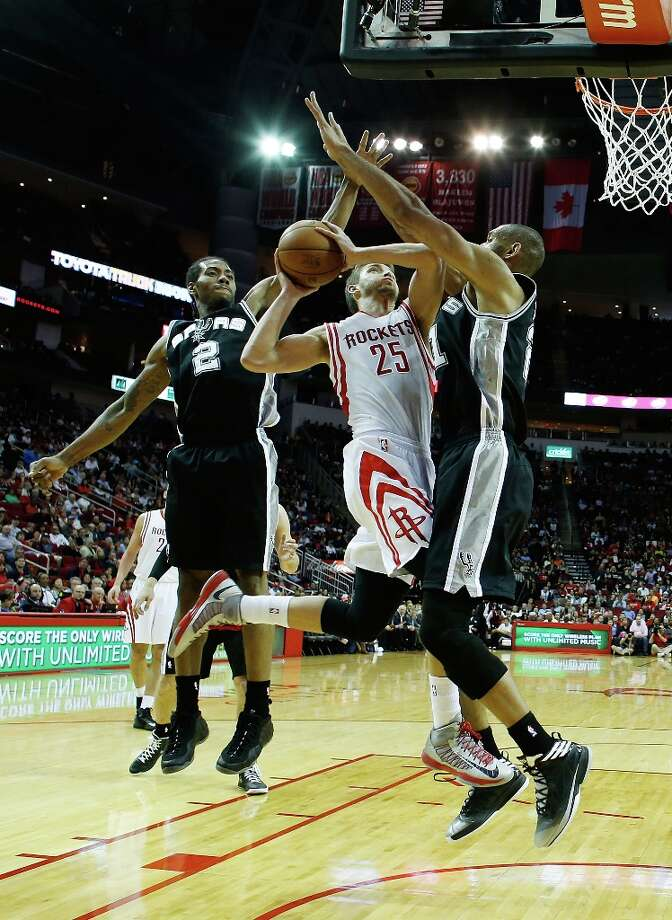 Chandler Parsons (25) of the Houston Rockets is defended by Kawhi Leonard (2) and Tim Duncan (21) of the Spurs at Toyota Center on March 24, 2013 in Houston. Photo: Scott Halleran, Getty Images / 2013 Getty Images