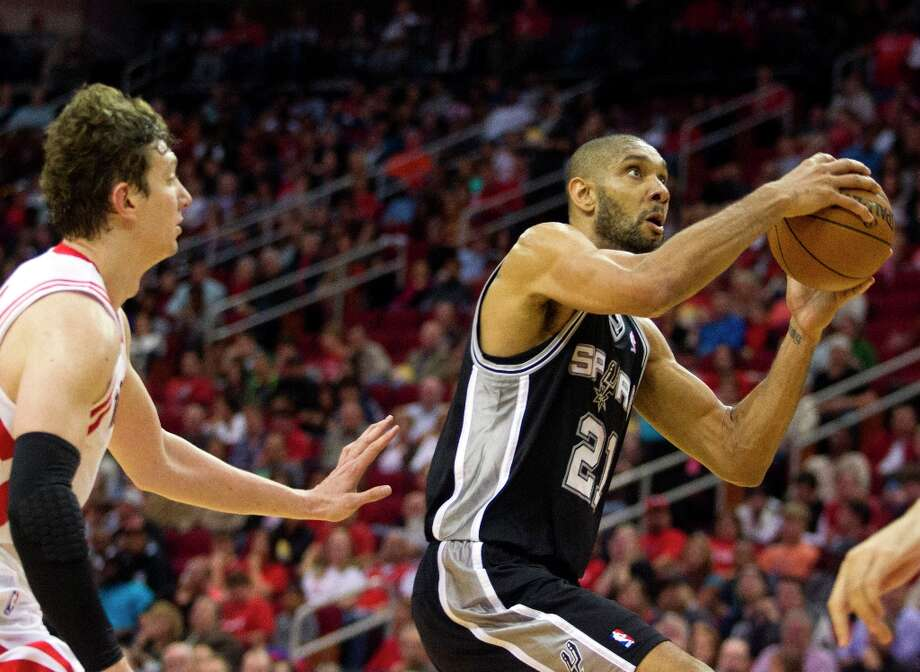 Spurs forward Tim Duncan (21) drives to the basket past Houston Rockets center Omer Asik (3) during the second half Sunday, March, 24, 2013 in Houston. Photo: Patric Schneider, Associated Press / FR170473 AP