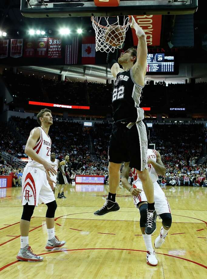 Tiago Splitter (22) of the Spurs dunks over Chandler Parsons (25) and Greg Smith (4) of the Houston Rockets at Toyota Center on March 24, 2013 in Houston. Photo: Scott Halleran, Getty Images / 2013 Getty Images