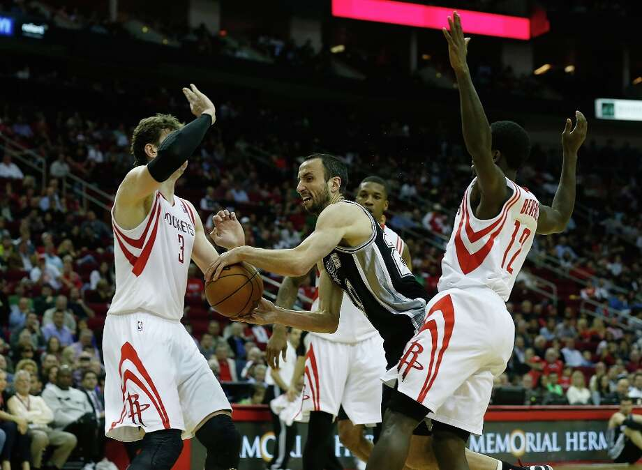 Manu Ginobili (20) of the Spurs looks to pass the ball between Omer Asik (3) and Patrick Beverly (12) of the Houston Rockets at Toyota Center on March 24, 2013 in Houston. Photo: Scott Halleran, Getty Images / 2013 Getty Images
