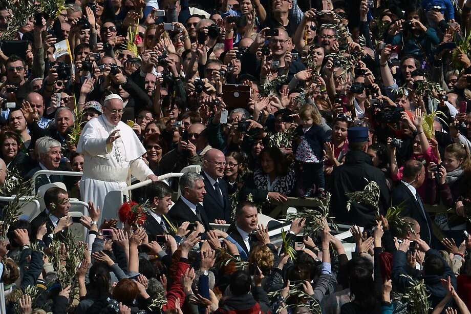 Pope Francis waves to the crowd from the papamobile after a mass on St Peter's square as part of the Palm Sunday celebration on March 24, 2013 at the Vatican. The Palm Sunday marks the start of the holy week of Easter in celebration of the crucifixion and resurrection of Jesus Christ.  Photo: Filippo Monteforte, AFP/Getty Images