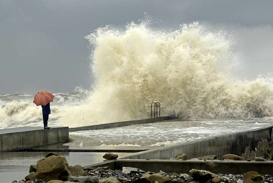 A woman stands on a pier under an umbrella during a storm in a Russian Black Sea resort of Sochi on March 24, 2013.  Photo: Mikhail Mordasov, AFP/Getty Images