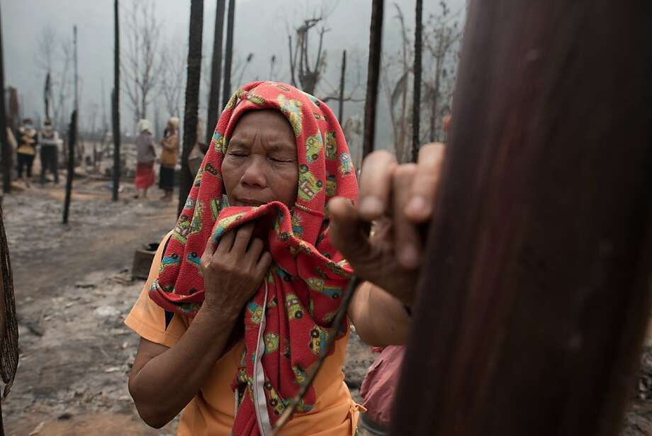 Myanmar refugee Thaku, 65, who is the only survivor of a family of five, looks from a distance where the bodies of her family are inspected by arsenic police for DNA samples at the Mae Surin camp in Mae Hong Son province on March 24, 2013. Thai rescue workers picked through the ashes of hundreds of shelters for Myanmar refugees, after a ferocious blaze swept through a camp in northern Thailand killing 35 people.  Photo: Nicolas Asfouri, AFP/Getty Images