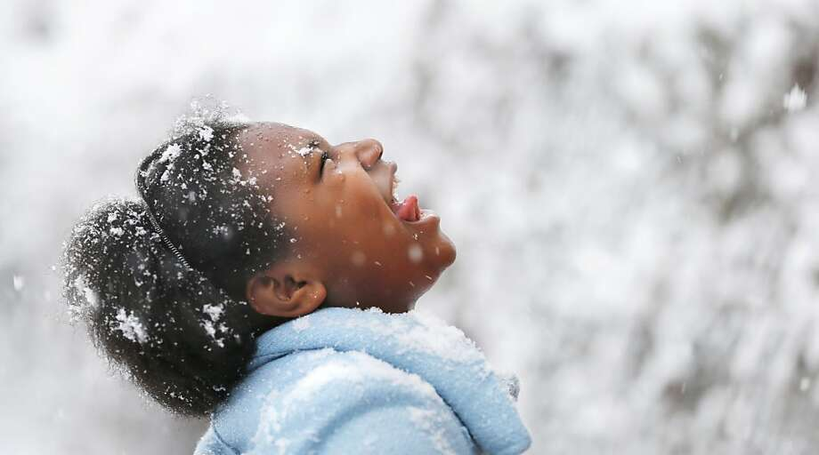 Destiny Chew, age 11, tries to catch snowflakes on her tongue as she stands along Q Street in Richmond, Va. Sunday, March 24, 2013. Photo: Alexa Welch Edlund, Associated Press