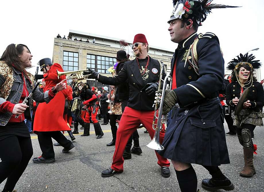 "Members of the Detroit Party Marching Band perform at the March du Nain Rouge in the Cass Corridor in Detroit on Sunday, March 24, 2013. The tradition features masked and costumed revelers taking to the city streets to banish the folkloric ""nain rouge"" or red dwarf from the city and save the city from its woes. ( Photo: Robin Buckson, Associated Press"