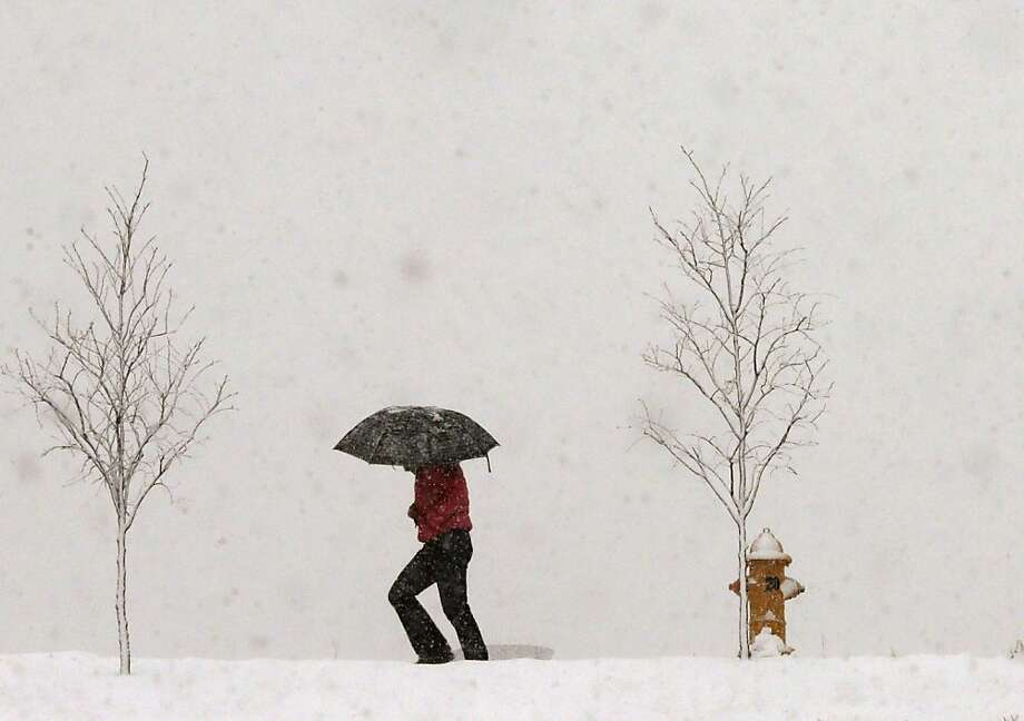 A person walks along Jayhawk Boulevard with an umbrella as snow from a winter storm begins to fall in Lawrence, Kan., Saturday, March 23, 2013.  Photo: Orlin Wagner, Associated Press