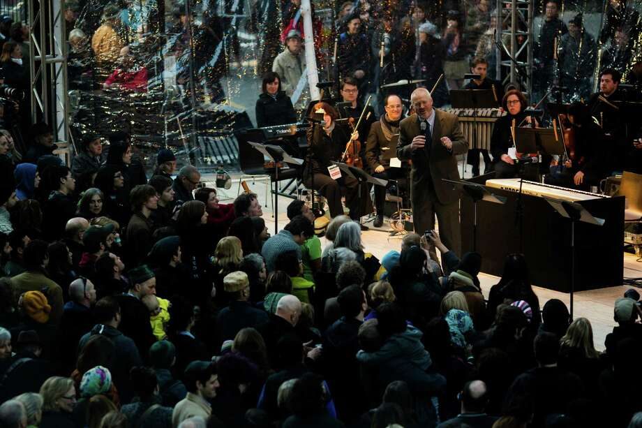 Seattle Mayor Mike McGinn, upper right, addresses a massive crowd before the unveiling of MIRROR, a permanent art installation for the façade of the Seattle Art Museum by artist Doug Aitken Sunday, March 24, 2013, in downtown Seattle. MIRROR is an urban earthwork that changes in real time in response to the movement, weather and life of the city around it. Photo: JORDAN STEAD / SEATTLEPI.COM