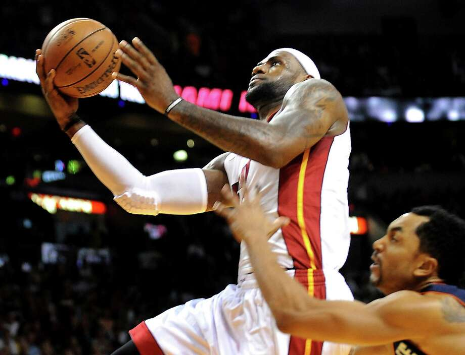 Miami's LeBron James drives to the basket past Charlotte guard Gerald Henderson en route to 32 points, eight rebounds and 10 assists in the Heat's 26th consecutive victory. Photo: Robert Duyos / McClatchy-Tribune News Service