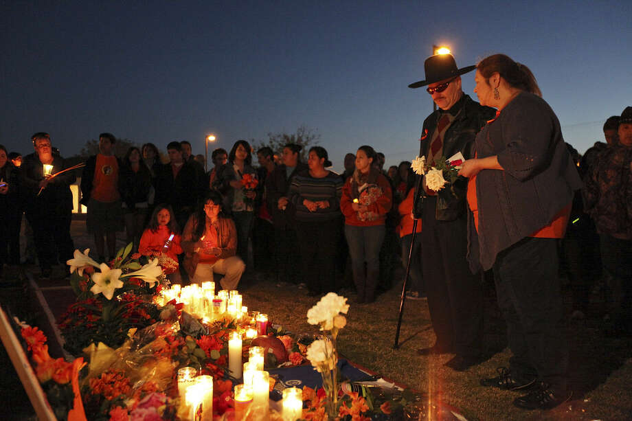 Matt Olmsted and Linda Garza, the parents of Alex Olmsted, attend a vigil for their son, a Jefferson High School senior, at the school's football field. He was killed in a collision with a tractor-trailer in Seguin on Saturday. Photo: Edward A. Ornelas / San Antonio Express-News
