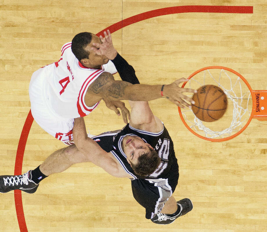 Rockets power forward Greg Smith (4) dunks the ball over Spurs center Tiago Splitter (22) during the second half. Photo: Smiley N. Pool, Houston Chronicle / © 2013  Houston Chronicle