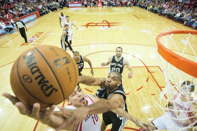 Rockets shooting guard Carlos Delfino drives to the basket as Spurs power forward Tim Duncan. Photo: Smiley N. Pool, Houston Chronicle / © 2013  Houston Chronicle