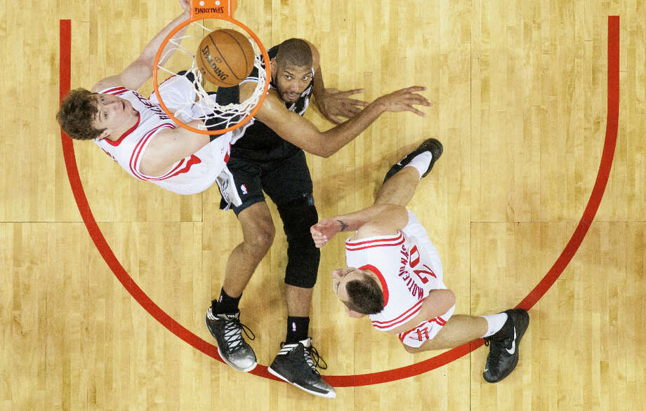 San Antonio Spurs power forward Tim Duncan watches as his shot goes into the net as he falls to  the floor between Houston Rockets center Omer Asik (3) and power forward Donatas Motiejunas. Photo: Smiley N. Pool, Houston Chronicle / © 2013  Houston Chronicle