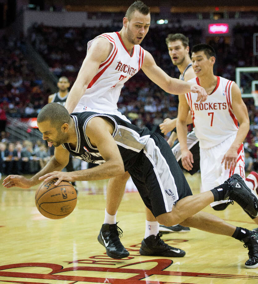 Spurs point guard Tony Parker falls to the floor as he is fouled by Rockets power forward Donatas Motiejunas. Photo: Smiley N. Pool, Houston Chronicle / © 2013  Houston Chronicle