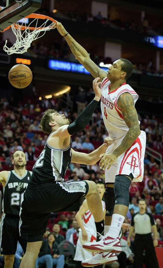 The Rockets' Greg Smith (4) puts the power in power forward, dunking over Spurs center Tiago Splitter (22) during the second half of Sunday night's game at Toyota Center. Photo: Smiley N. Pool, Staff / © 2013  Houston Chronicle